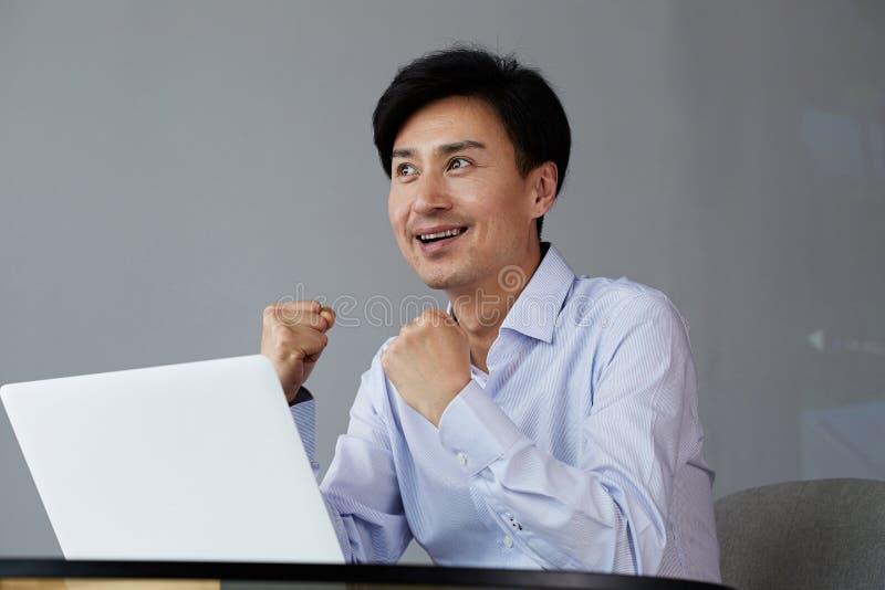 fira framg?ng Upphetsade unga asiatiska affärsmanarmar upp, medan arbeta på kontoret med bärbara datorn arkivbilder