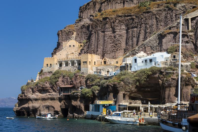 FIRA, GREECE - JUNE 16, 2019: Beautiful view of the Old Port in Fira town with the sailboat  ship in the foreground, Santorini,. Greece stock images