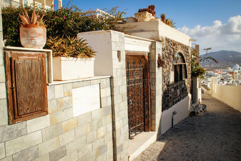 Fira grodzka ulica z biel ścianą i domami wyspy Oia santorini zdjęcia stock