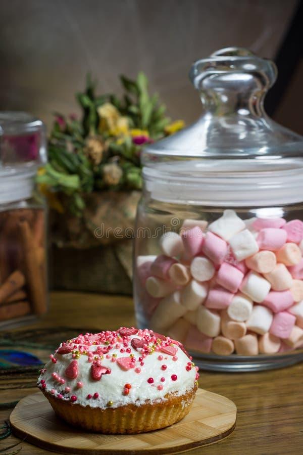 Fira marshmallowen, blommar muffin på trätabellen, födelsedagpartiet arkivfoton
