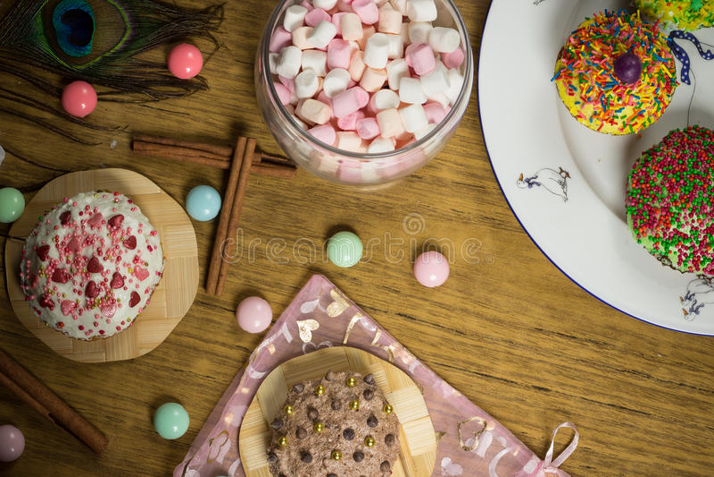 Fira marshmallowen, kaka, godisar, fruktte på trätabellen, födelsedag royaltyfri fotografi
