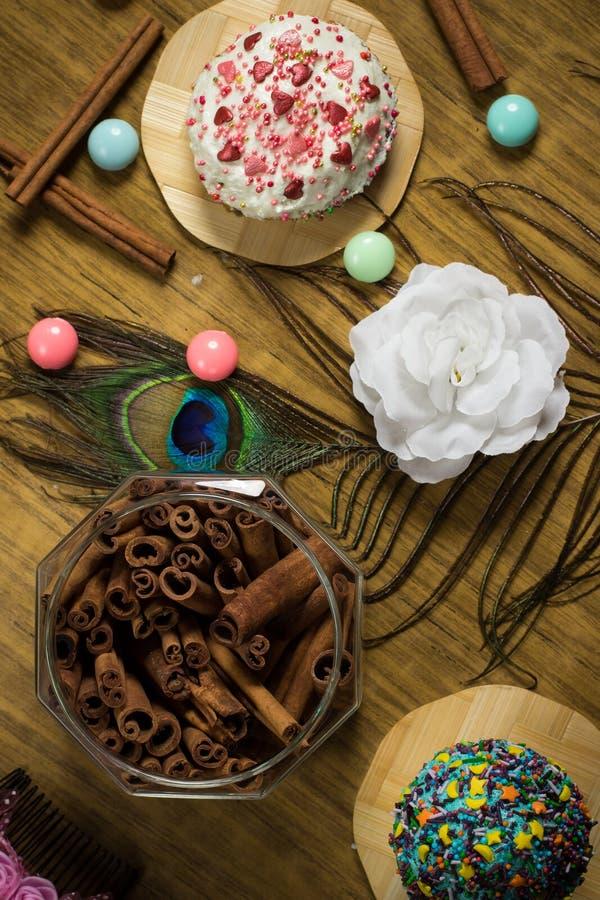 Fira söta muffin, kanelbrun garnering på trätabellen, födelsedagparti royaltyfria foton