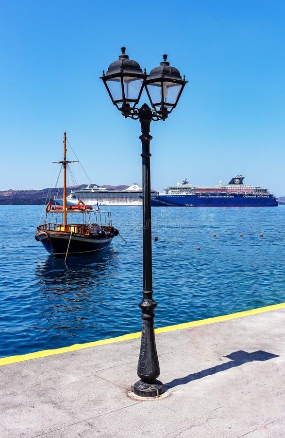 Fira, Santorini/Griechenland - 05-25-2014: zwei große Kreuzschiffe und ein altes Boot im kleinen Hafen von Fira, Santorini, Griec lizenzfreies stockfoto