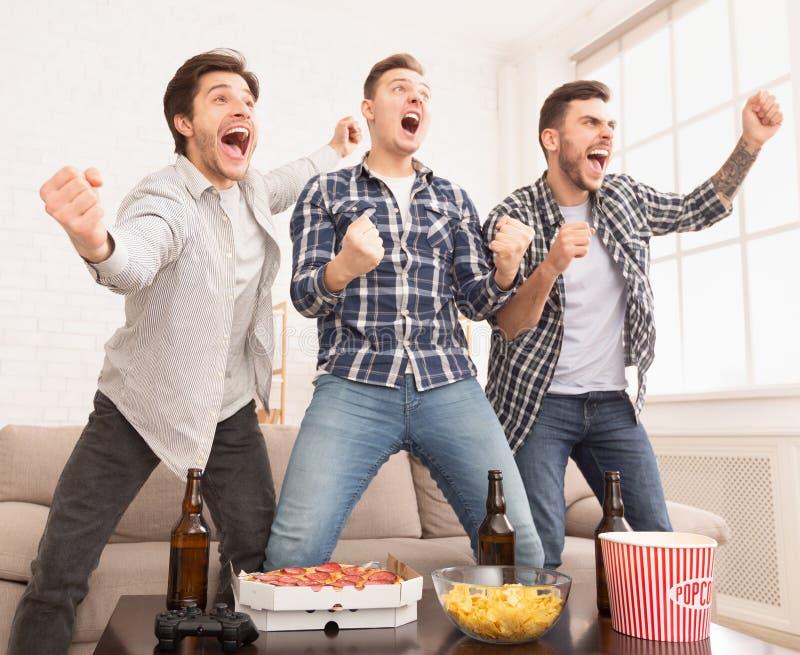 fira seger Lyckliga fotbollsfan som håller ögonen på fotboll på tv arkivfoto