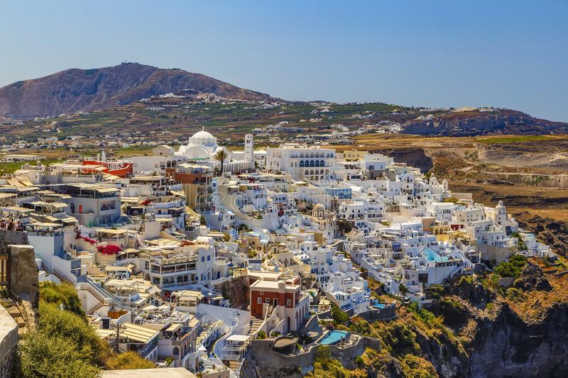 Fira town, Santorini island in Greece. Landscape with white buildings. Incredibly romantic top view of Oia village with mountai. N on background stock image