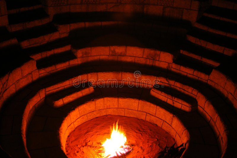 Fire 02. A campfire burning in an boma which was dug into the ground. This is lined with steps and seats. This method is used in Africa to isolate yourself from royalty free stock photography