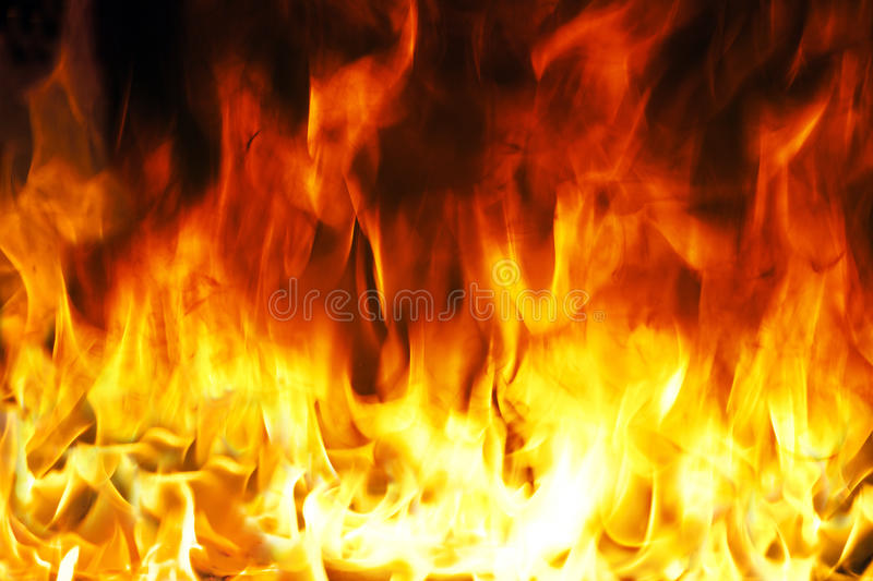 Fire. And flames with a burning dark red-orange background royalty free stock photos