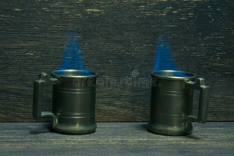 Fire above metal mugs stock image