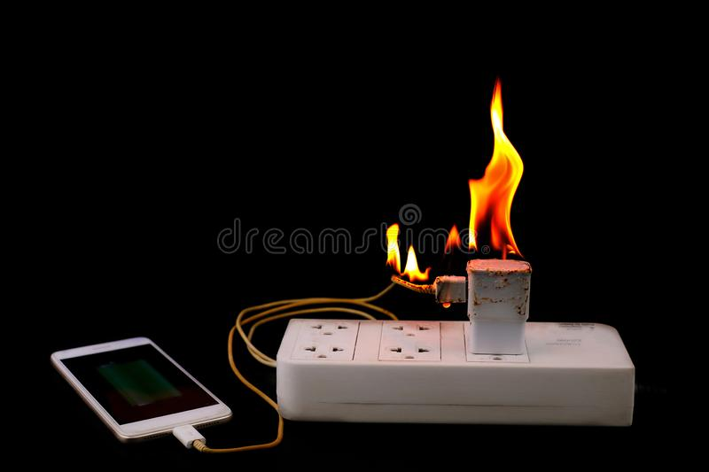 On fire Adapter smart phone charger at plug in power outlet royalty free stock photo