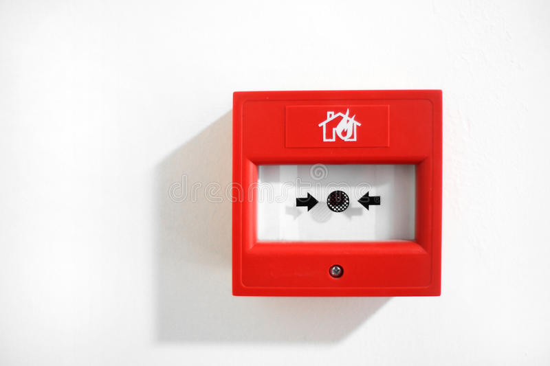 Fire alarm. Red fire alarm on white wall stock photography