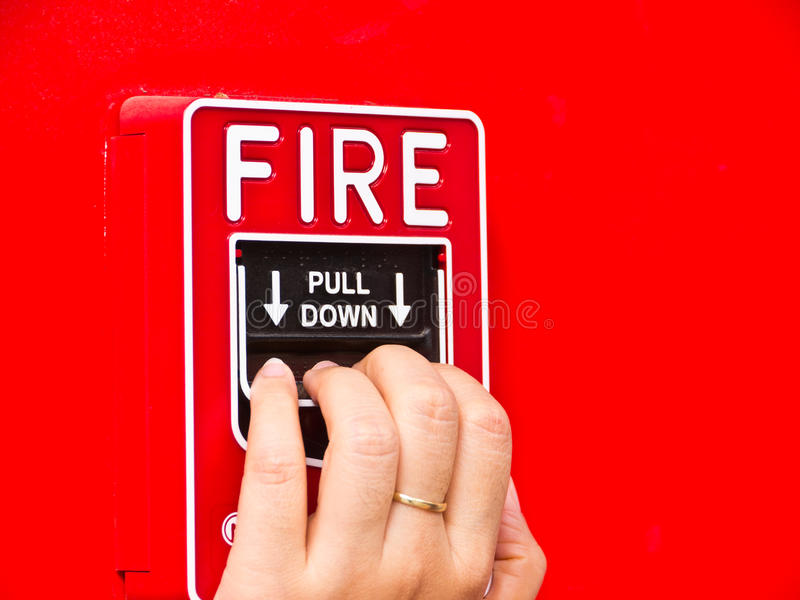 Fire alarm. Hand on fire alarm box on red wall stock photo