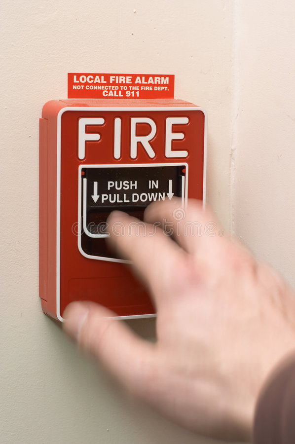 Fire Alarm Being Pulled. Hand in motion pulling to activate fire alarm stock images