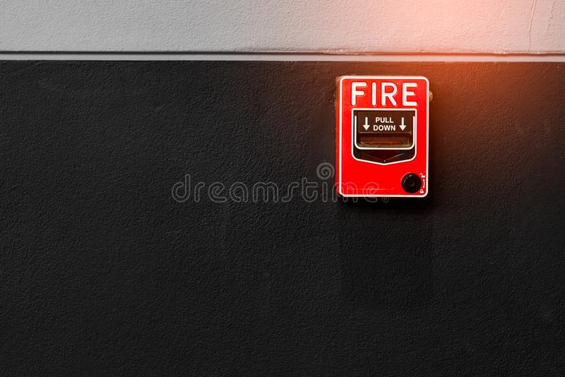Fire alarm on black and white concrete wall. Warning and security system. Emergency equipment for safety alert. Red box of fire royalty free stock photo