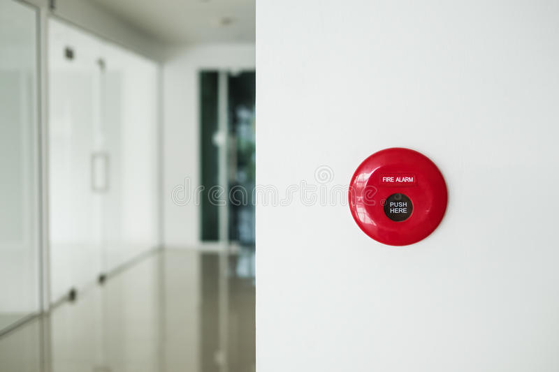 Fire alarm, emergency button on white wall in modern office stock image