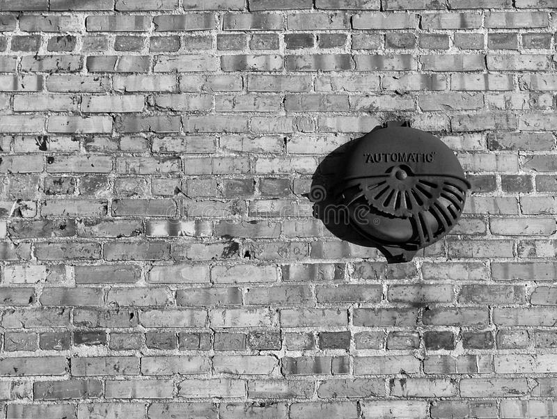 Fire alarm sprinkler. Automatic fire alarm sprinkler against a weathered brick wall in black and white desaturated stock image