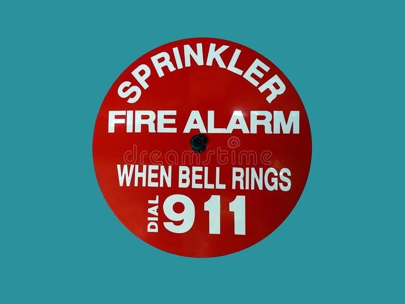 A fire alarm on a wall informing that a sprinkler will operate when the bell rings. A fire alarm on a wall in the USA informing that a sprinkler will operate royalty free stock photography