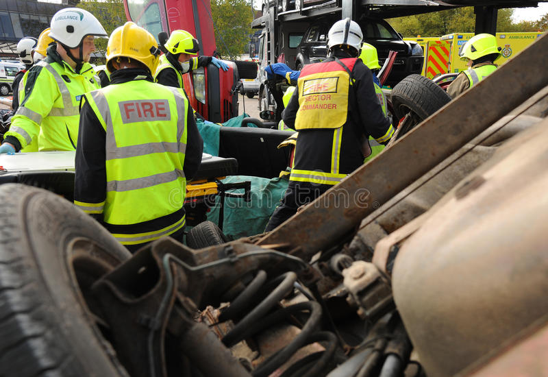 Fire and ambulance crews with overturned car. Fire service officer cutting away a car roof at the scene of a car crash exercise Suitable for emergency service stock images
