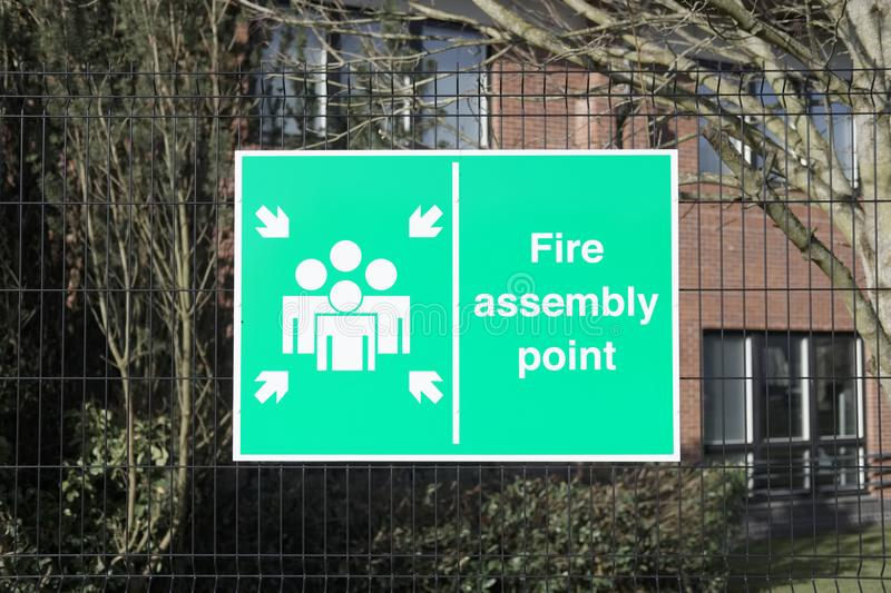 Fire assembly point sign at office workplace factory for safety security of workers people employees stock image