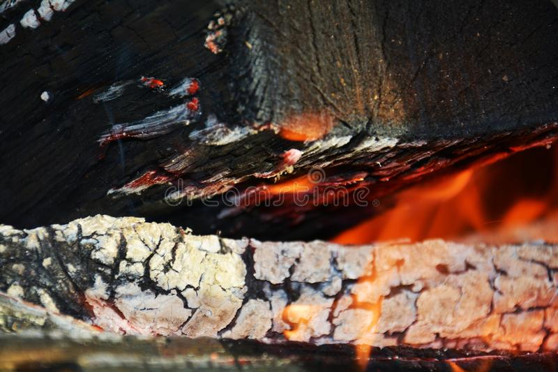 Fire. Wood dark hard logs burning, orange flames and hot temperature royalty free stock photo