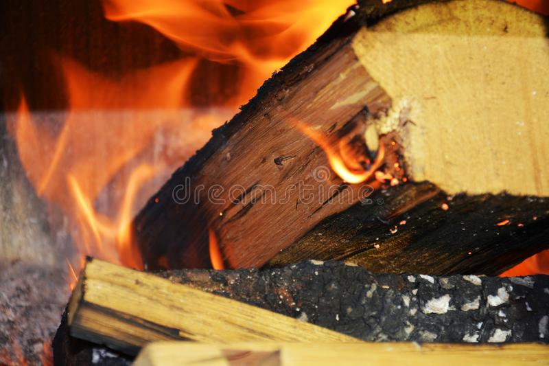 Fire. Wooden dark logs burning, orange flames and hot temperature royalty free stock photography
