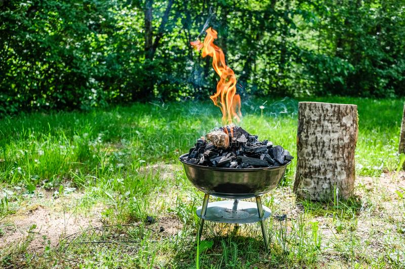 Fire on barbecue charcoal grill. Grilling food on a weber type s. Mall cheap BBQ grill at home. Family backyard barbecue - BBQ picnic stock image
