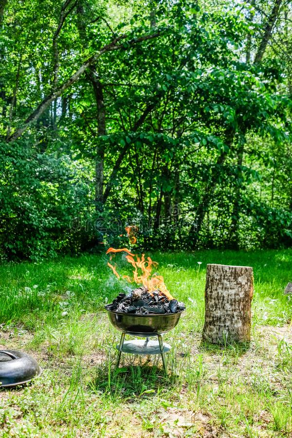 Fire on barbecue charcoal grill. Grilling food on a weber type s. Mall cheap BBQ grill at home. Family backyard barbecue - BBQ picnic royalty free stock photo
