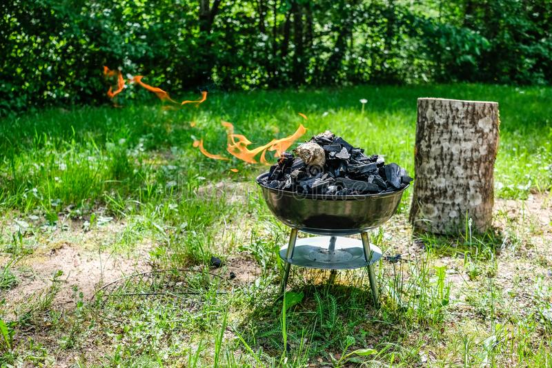 Fire on barbecue charcoal grill. Grilling food on a weber type s. Mall cheap BBQ grill at home. Family backyard barbecue - BBQ picnic stock images