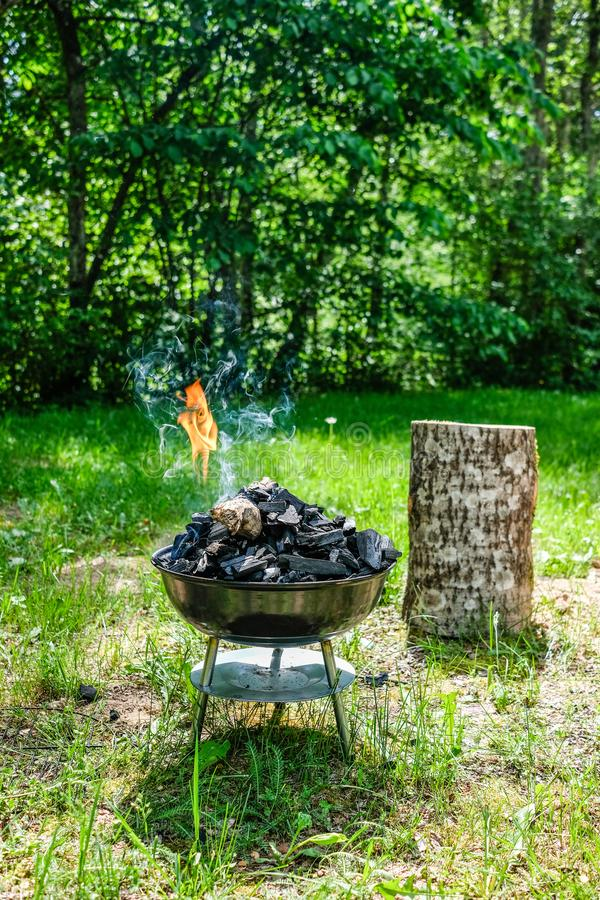 Fire on barbecue charcoal grill. Grilling food on a weber type s. Mall cheap BBQ grill at home. Family backyard barbecue - BBQ picnic royalty free stock photos