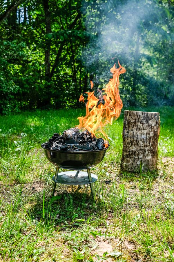 Fire on barbecue charcoal grill. Grilling food on a weber type s. Mall cheap BBQ grill at home. Family backyard barbecue - BBQ picnic royalty free stock image