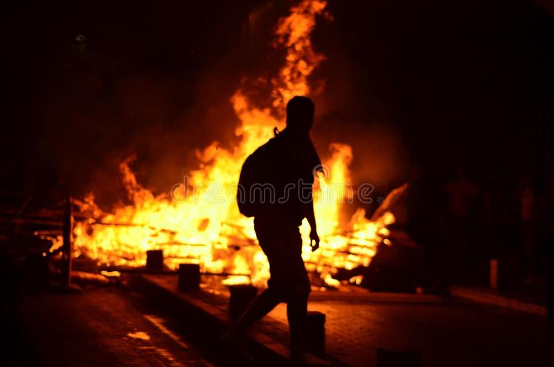 Fire and barricade. A protestoant passing by fire on the barricade during clashes in Istanbul known as Gezi Park protests stock images