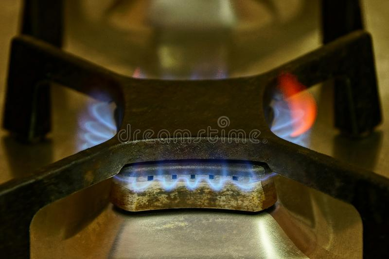 Fire from a black gas burner on an iron plate stock photography