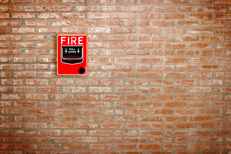 Fire break glass alarm switch on brick wall background stock photos
