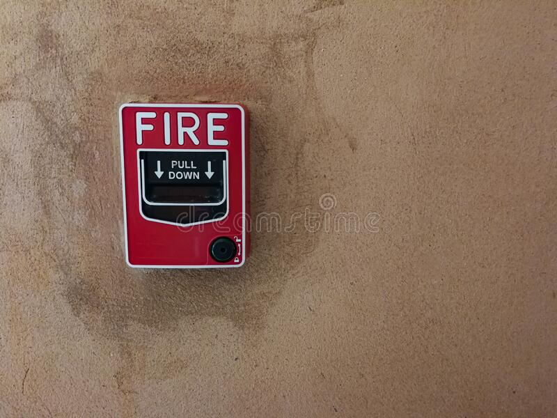 Fire break glass alarm switch on the concrete wall. Fire break glass alarm switch on the red concrete wall stock photos