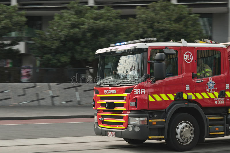 Fire brigade truck. Red fire brigade truck with crew in cabin motion on road with green trees blurred in background and Melbourne city reflection on windscreen stock image