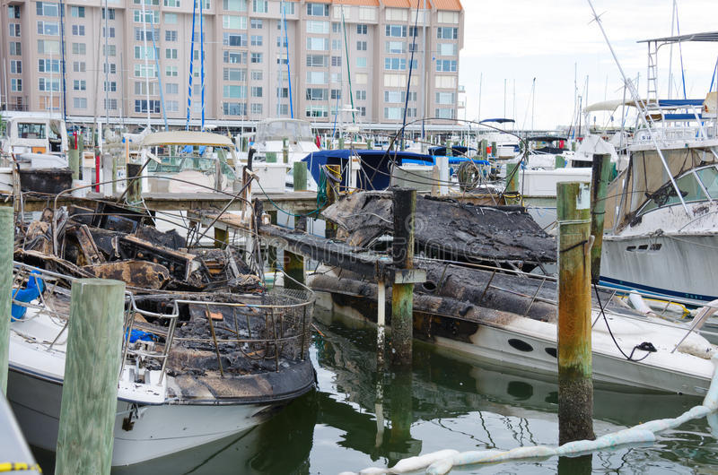 Fire burned boats accident at marina. Two boats are severely burned after a huge boat fire and are sinking at a marina dock royalty free stock photos