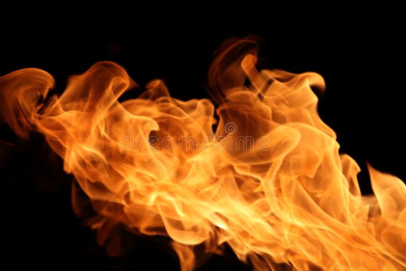 Fire burning on dark background for abstract flame texture and graphic design purpose. Fire burning on dark background for abstract flame texture and graphic stock photo