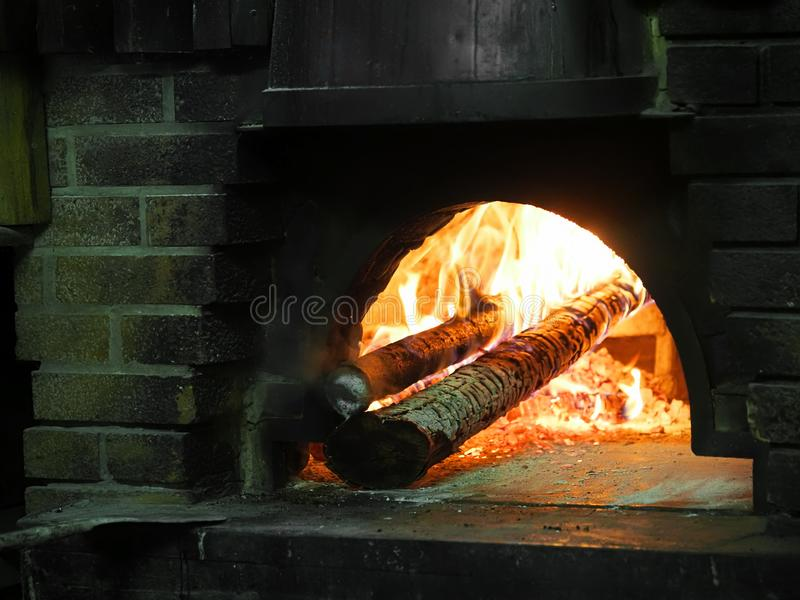 Fire burning with logs inside old fashioned, traditional brick pizza oven. Italy. stock images