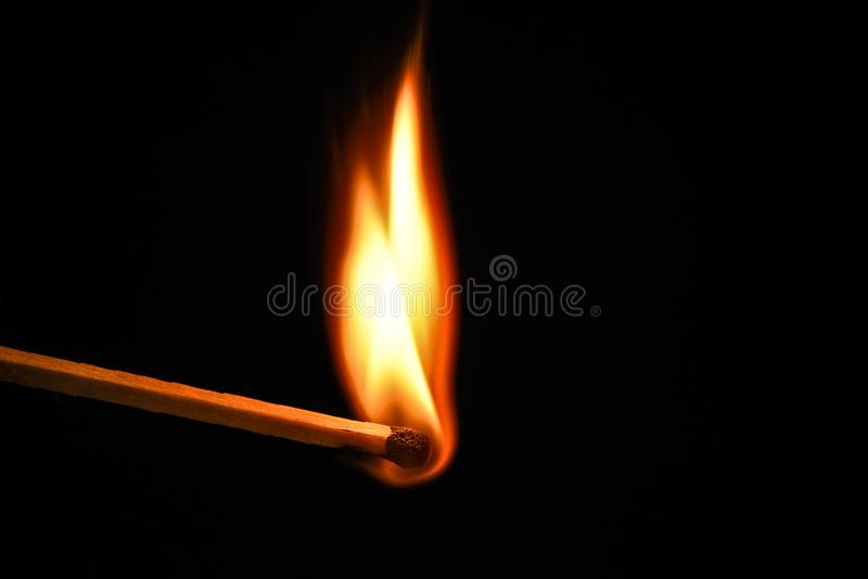 Fire burning on matchstick. Isolated on black background. stock photography