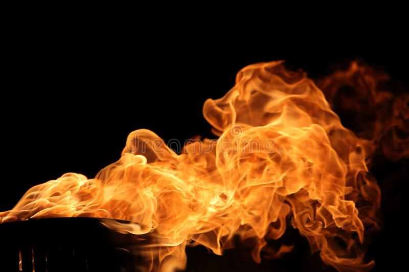 Fire burning on torch with dark background for abstract flame texture and graphic design purpose. Fire burning on torch with dark background for abstract flame stock photos