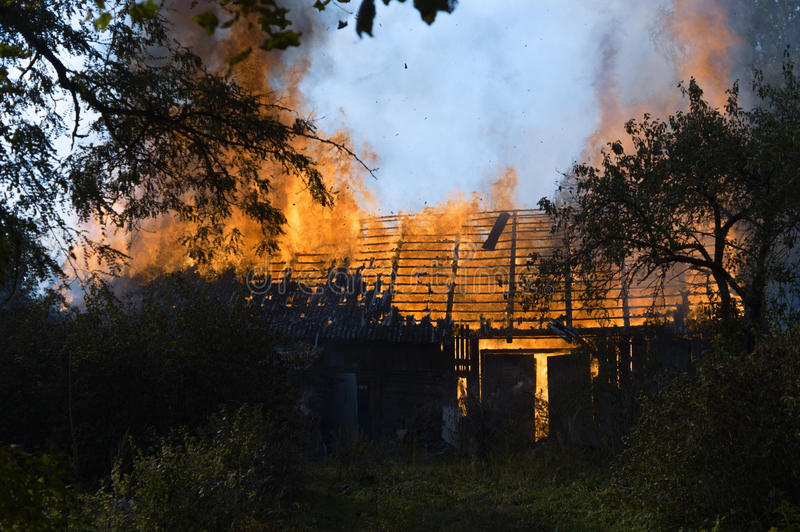 The fire is burning wooden house stock photo