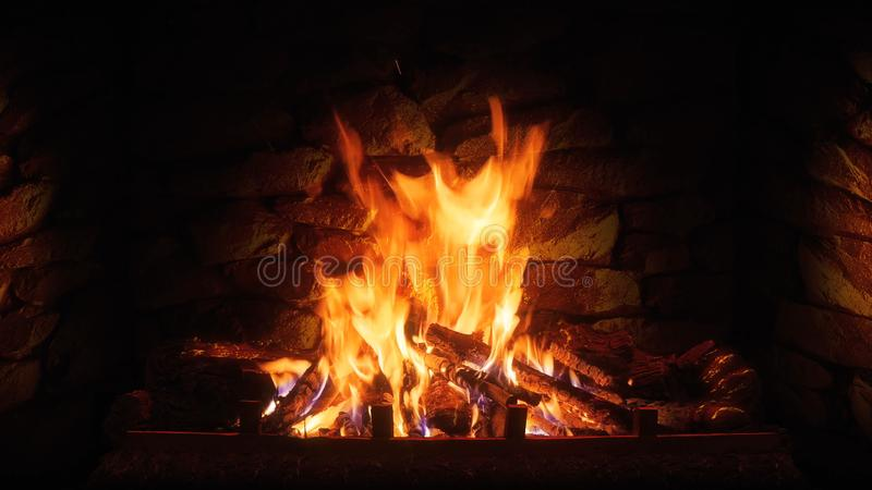 The fire burns in the home fireplace. Coziness in the house stock photography