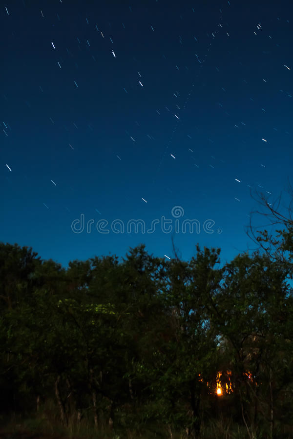 A fire burns inside the forest in a full moon night with an Ursa Major constellation star trails stock photo