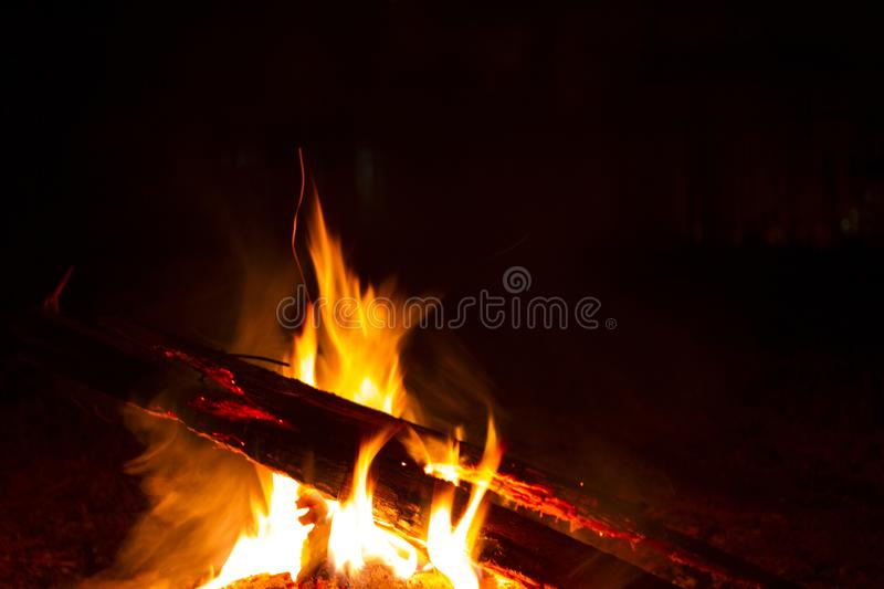 Fire burns at night. Many wooden planks are stacked together and a fire is burning. The time and place of the action - street, night, village, Krolevets stock photo