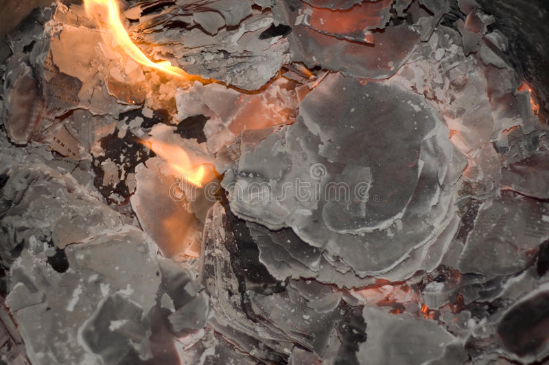Fire burns paper to ash. Visible flames as fire burns paper to charcoal coloured ash royalty free stock photos