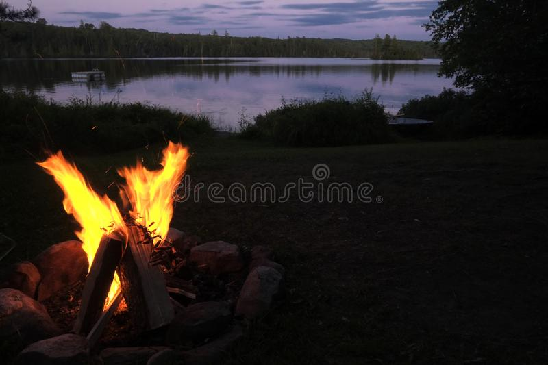 Fire camp beside a lake at sunset. Fire camp at Black Lake in Nominingue, Quebec, Canada with nice sunset stock images