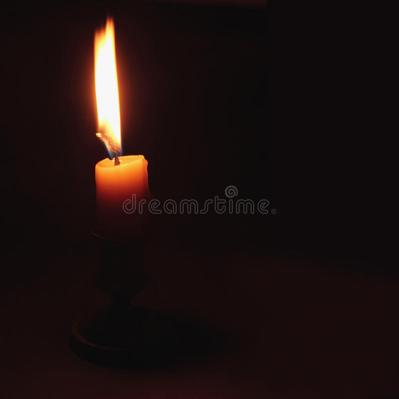 Fire candle on a dark background royalty free stock images