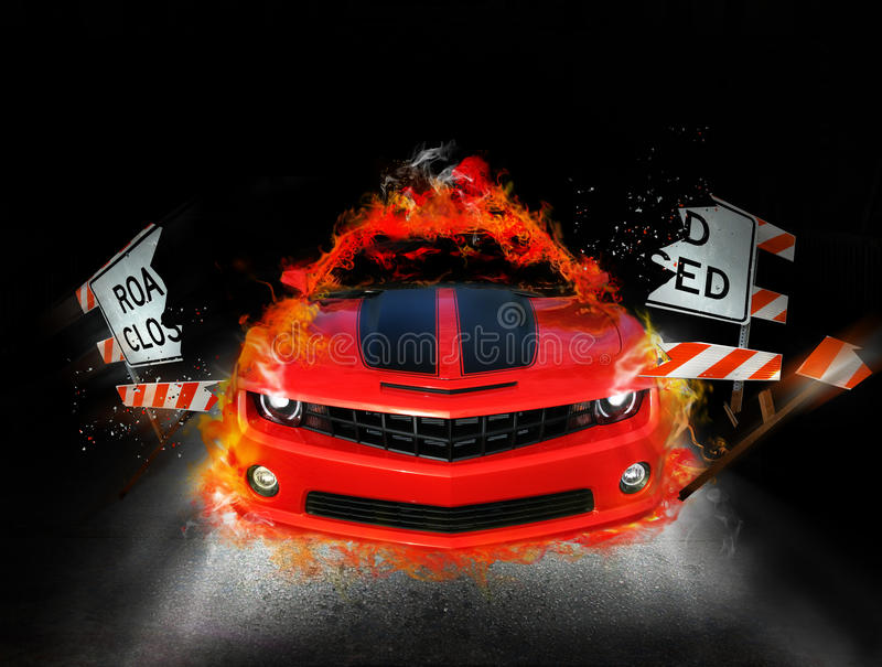 Fire car. A bright orange red Chevrolet Camaro automobile busts through a road closed sign breaking it in two. Fire and flames come from sides and roof of the