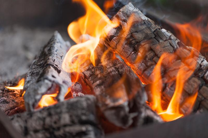 Fire with charcoals. Burning wood. Macro. Live flames with smoke. Wood with flame for barbecue and cooking bbq. Bright color. Orange royalty free stock photography