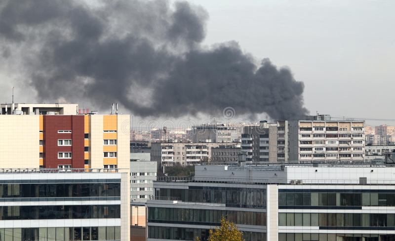 A fire in the city. The smoke from the fire spreading over the city royalty free stock images