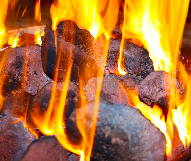 Fire and coals. Closeup of lava rocks in a fire pit royalty free stock photography